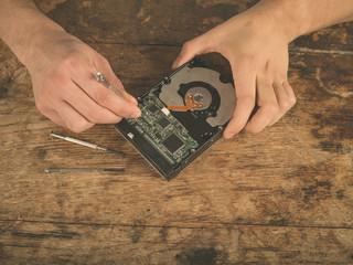 Hands fixing a harddrive on desk