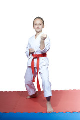 Little girl in a white clothes standing on the mat