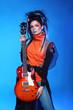 Punk girl guitarist posing over blue studio background. Trendy r