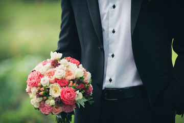 groom holding bridal bouquet on a green background