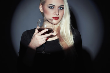 Beautiful blond woman with red wine.wineglass.drinking girl