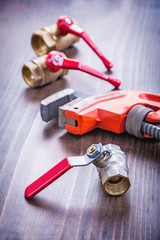adjustable wrench and plumbing fixtures on vintage wooden board