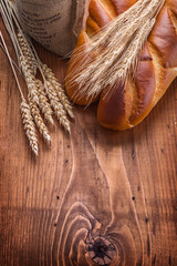 bguettes and wheat ears on vintage wooden board with copyspace f