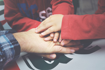 manos de un padre con sus hijos
