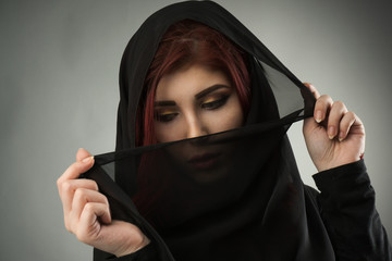 Young muslim woman covering her face and hair with a black veil
