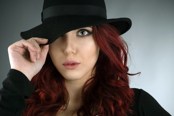 Young woman covering her eye with a fedora hat