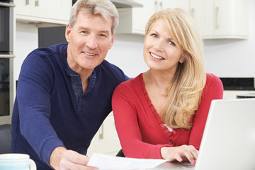 Smiling Mature Couple Reviewing Domestic Finances
