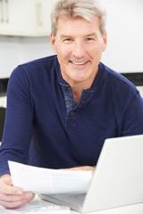 Smiling Mature Man Reviewing Domestic Finances