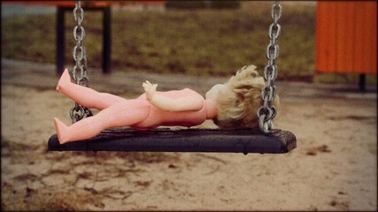 Old abandoned doll on a swing in retro style