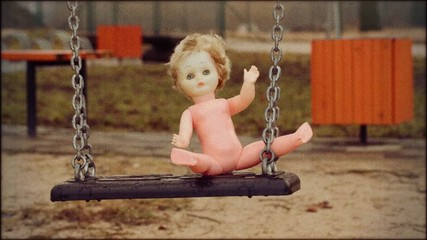 Abandoned doll on a swing in retro style