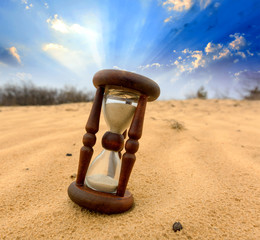 Hourgass in desert on sand