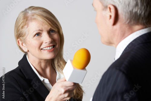 Female Journalist With Microphone Interviewing Businessman - 79363053