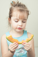 little girl eating a slice of cantaloupe
