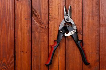open scissors on wood background