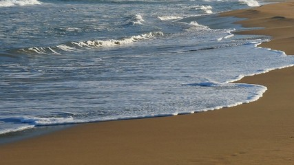 Waves on sandy beach. Slow motion