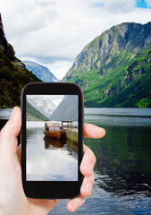 tourist taking photo of fjord in Norway