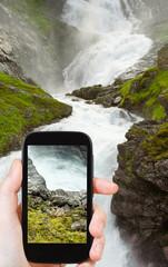 tourist taking photo of kjosfossen waterfall