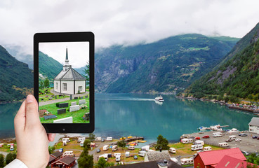 tourist taking photo of geiranger village