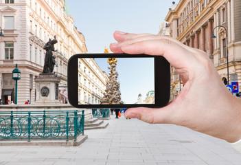 tourist taking photo of plague column in Vienna