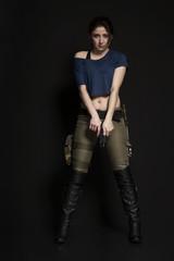 Frau mit Waffen vor dunklem Hintergrund