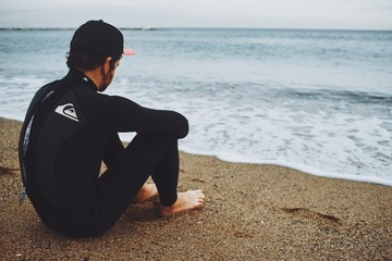 surfer watches sea while sitting on the shore