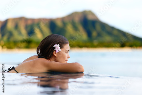 Infinity pool resort woman relaxing at beach