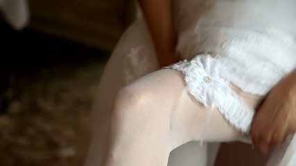 The bride wears a wedding garter on the leg