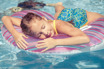 little girl lying on the  inflatable rubber circle  in the swimm