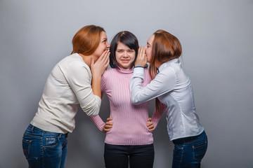 Three girls girlfriends talking in his ear, a secret on gray