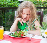 Child with disgust looking at salad
