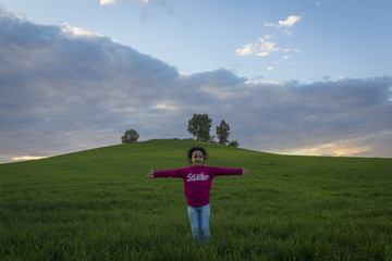 Niña disfrutando de la puesta de sol en el campo