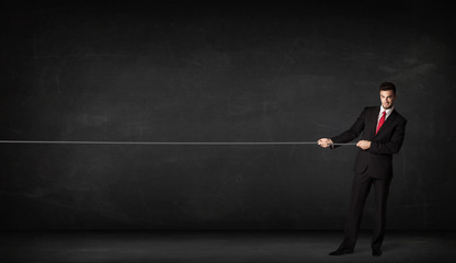 Businessman pulling rope on grey background