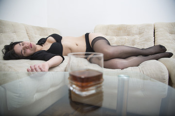 Sexy woman in black underwear lying drunken on the sofa