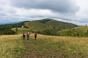 Trekking path through prairie grass at mountains and hills