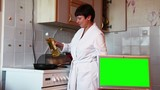 Woman prepares food in the kitchen. Green screen.