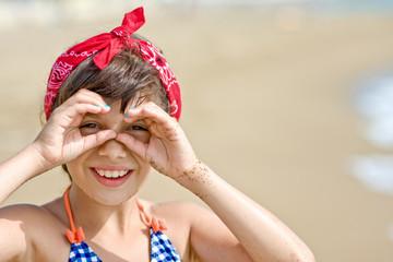 Girl looking through imaginary binocular on beach