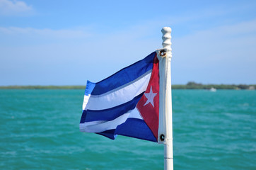 The flag of Cuba with  turquoise sea background.