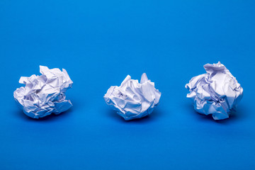 Three wrinkled white pieces of paper over a blue background.