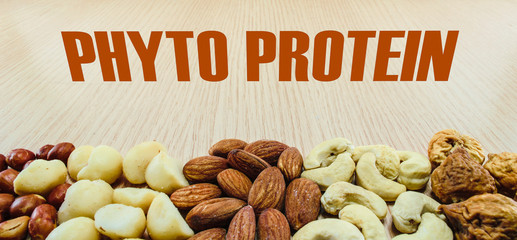 Mixed nuts on wood background with word phyto protein