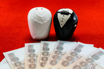 bride and groom with bank note for wedding cost concept