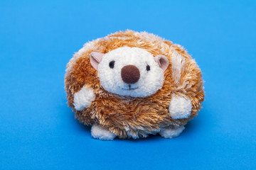 Cute small stuffed hedgehog toy over a blue background.
