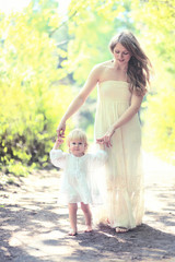 Sunny photo mother and child walking barefoot in the forest
