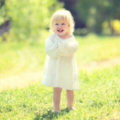 Sunny child having fun on the grass in summer day