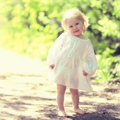 Sunny portrait of cute barefoot child on nature in summer day