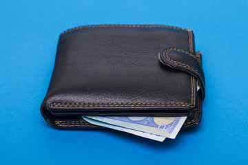 Close up view of a pocket money wallet over a blue background.