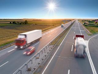 Trucks and car on the freeway at sunrise