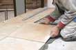 Home improvement, renovation - handyman laying tile with level - 79394432