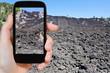 tourist taking photo of lava flow on slope of Etna