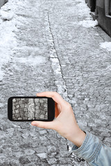 tourist taking photo of snowy cobblestone road
