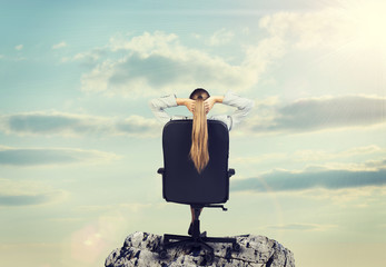 Woman with long hair sitting on chair, looking at sun. Backdrop